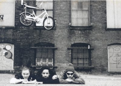 Red Eye 9 photo shoot. Ghost jumping a kiddie bike over us, Evil Kenievel style. Boston, MA. 1995